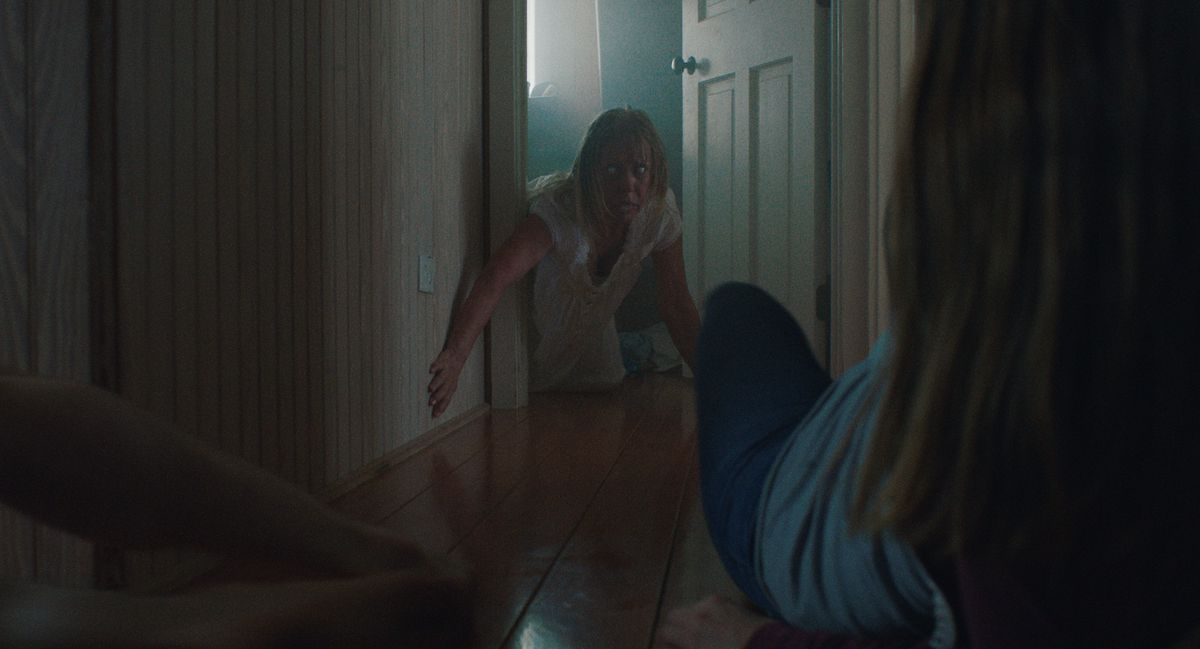 A blank-eyed woman in a nightgown crawls through a doorway toward another character in The Beach House.