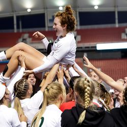 Olympus' Emma Neff, who scored the winning goal in extra time, is lifted up as the team celebrates their win over Bonneville in the 5A girls soccer state championship at Rio Tinto Stadium in Sandy on Friday, Oct. 23, 2020.