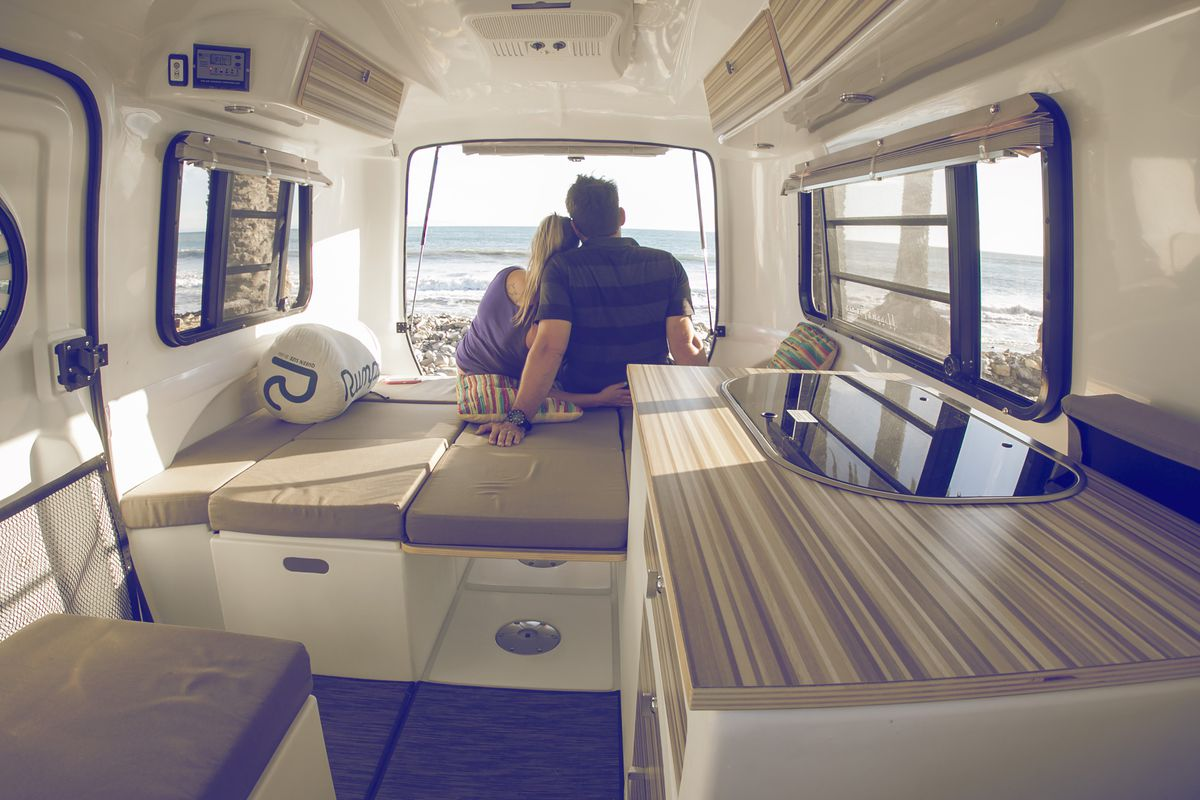 A couple sits inside a fiberglass camper looking out at the ocean.