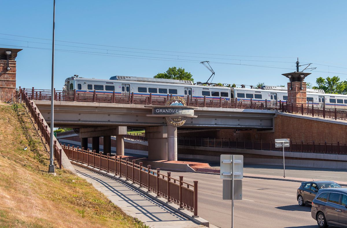 An electric commuter rail train runs over a bridge that spans a multi-lane highway.