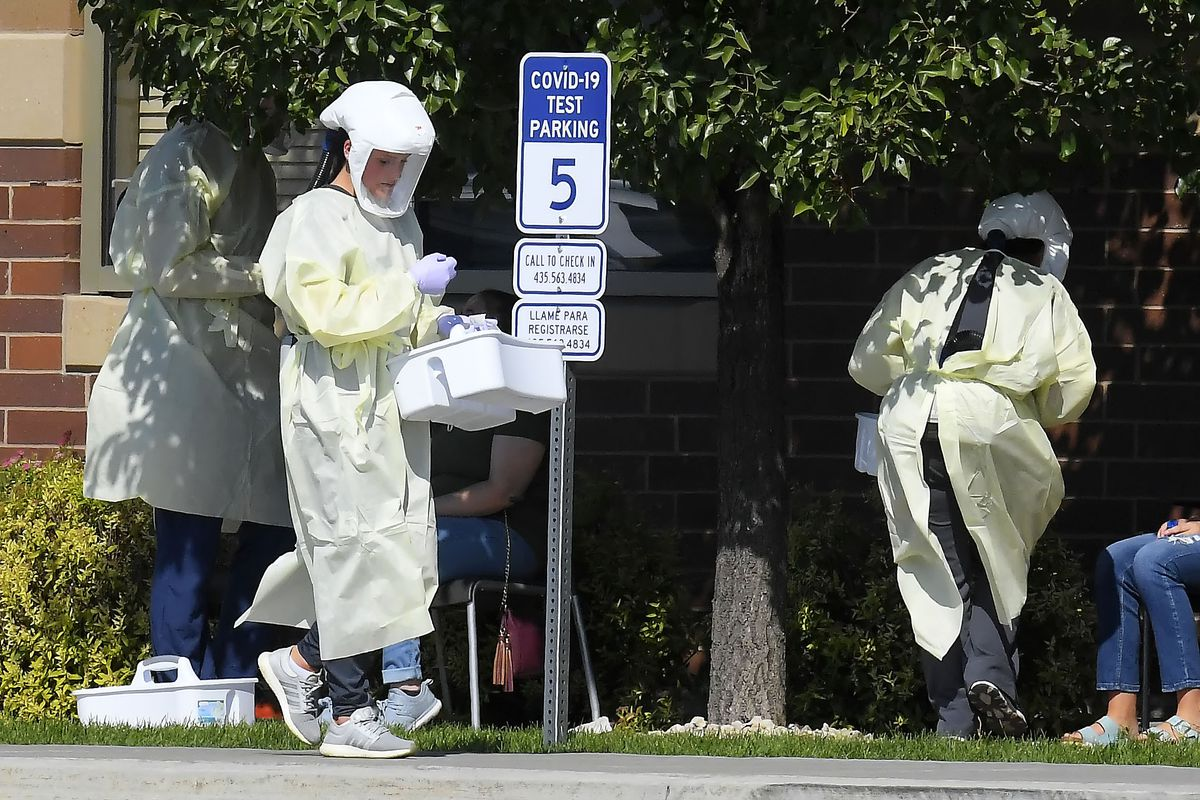 Workers test Utah State University students for COVID-19 on Sunday, Aug. 30, 2020, in Hyde Park, Utah. Students from four dorms were tested and quarantined after the virus was detected in the wastewater from those buildings.