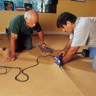 Men Seam Together Carpet Using Electric Seaming Iron, Seaming Weight And Seam Tape
