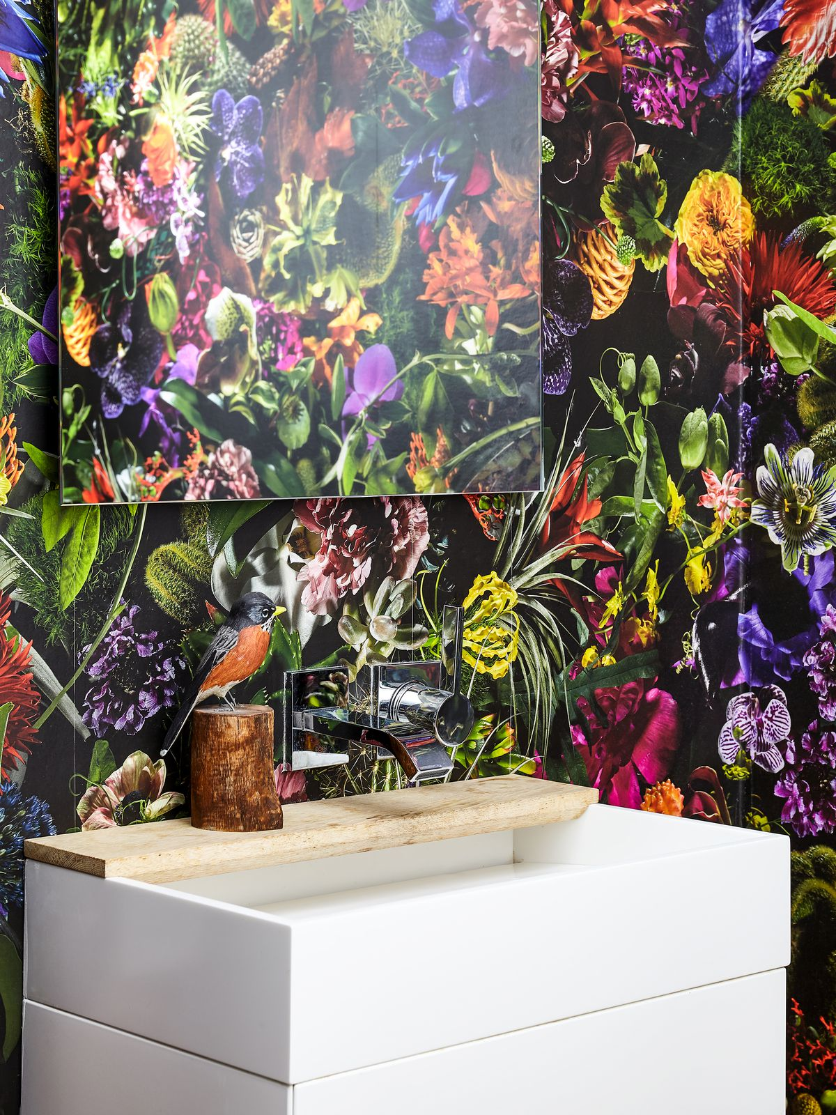 Ultra-busy dark-grounded floral wallpaper on a bathroom wall behind the mirror and sink. Photograph.