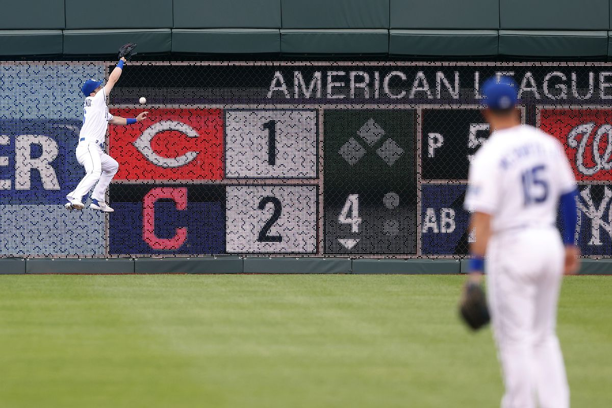 Andrew Benintendi #16 of the Kansas City Royals misses a fly ball at the wall during the 1st inning of the game against the Chicago White Sox at Kauffman Stadium on May 07, 2021 in Kansas City, Missouri.