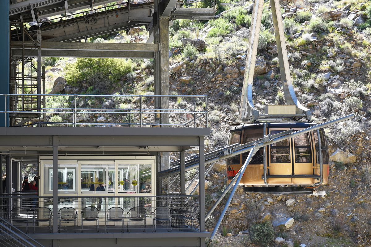 The Palm Springs Aerial Tramway. The tram is gold and is on a cable as it pulls into the docking station.