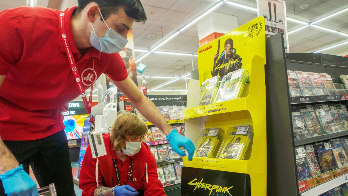 store employees wearing face masks and gloves adjust a Cyberpunk 2077 display