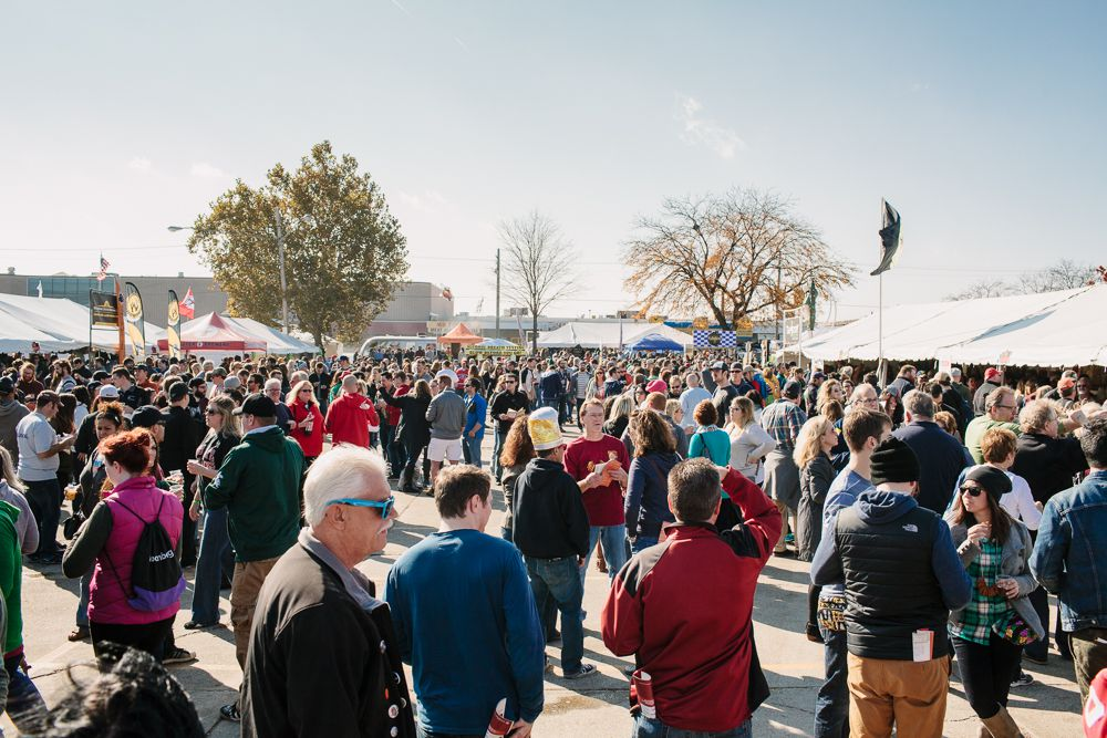 A large group of people walk between beer tents on a sunny day at Eastern Market.