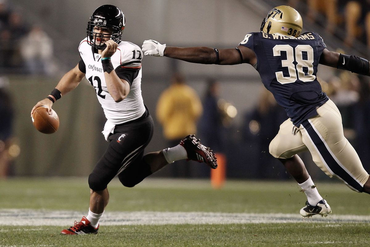PITTSBURGH, PA - NOVEMBER 05:  Zach Collaros #12 of the Cincinnati Bearcats escapes a tackle from Greg Williams #38 of the Pittsburgh Panthers on November 5, 2011 at Heinz Field in Pittsburgh, Pennsylvania.  (Photo by Jared Wickerham/Getty Images)