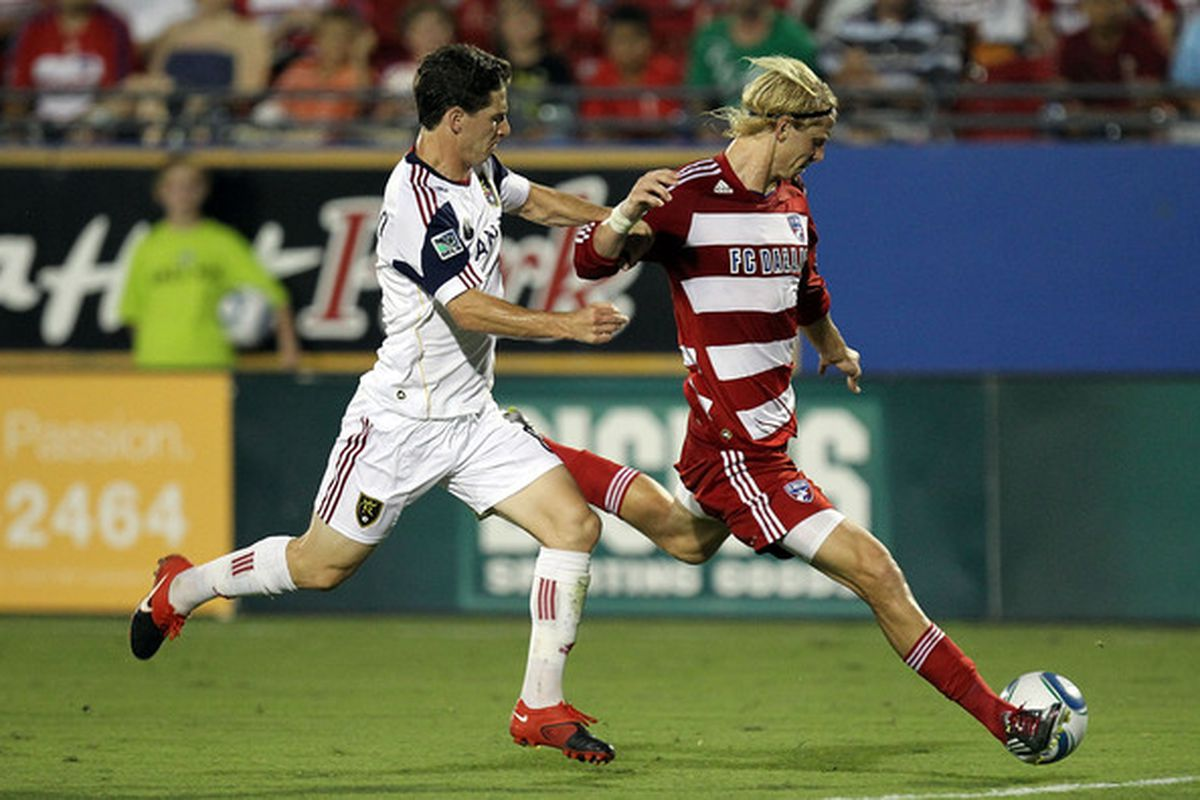 FRISCO TX - JULY 17:  Midfielder Brek Shea #20 of FC Dallas dribbles the ball past Will Johnson #8 of Real Salt Lake at Pizza Hut Park on July 17 2010 in Frisco Texas.  (Photo by Ronald Martinez/Getty Images)