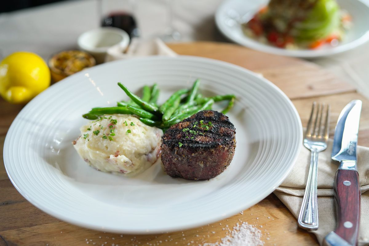 Filet mignon, a scoop of mashed potatoes, and green beans are artfully displayed on a white plate.