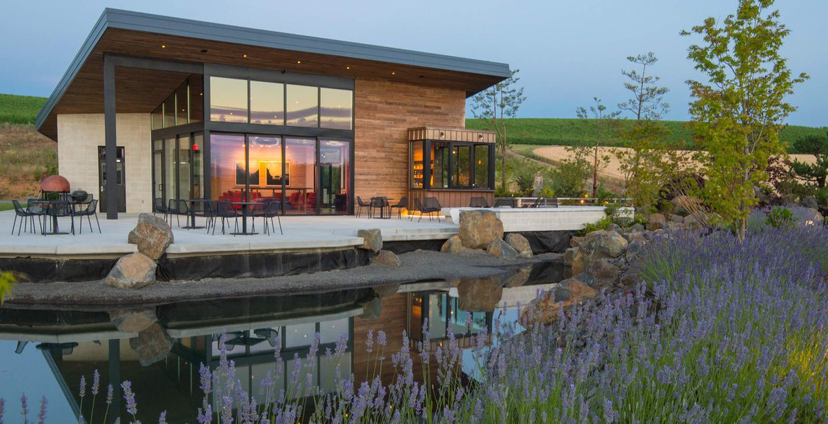 The exterior of Saffron Fields Winery in Oregon. There is a still water pool in the foreground surrounded by purple flowers. The building is glass and brown wood. There are tables and chairs in front of the building.