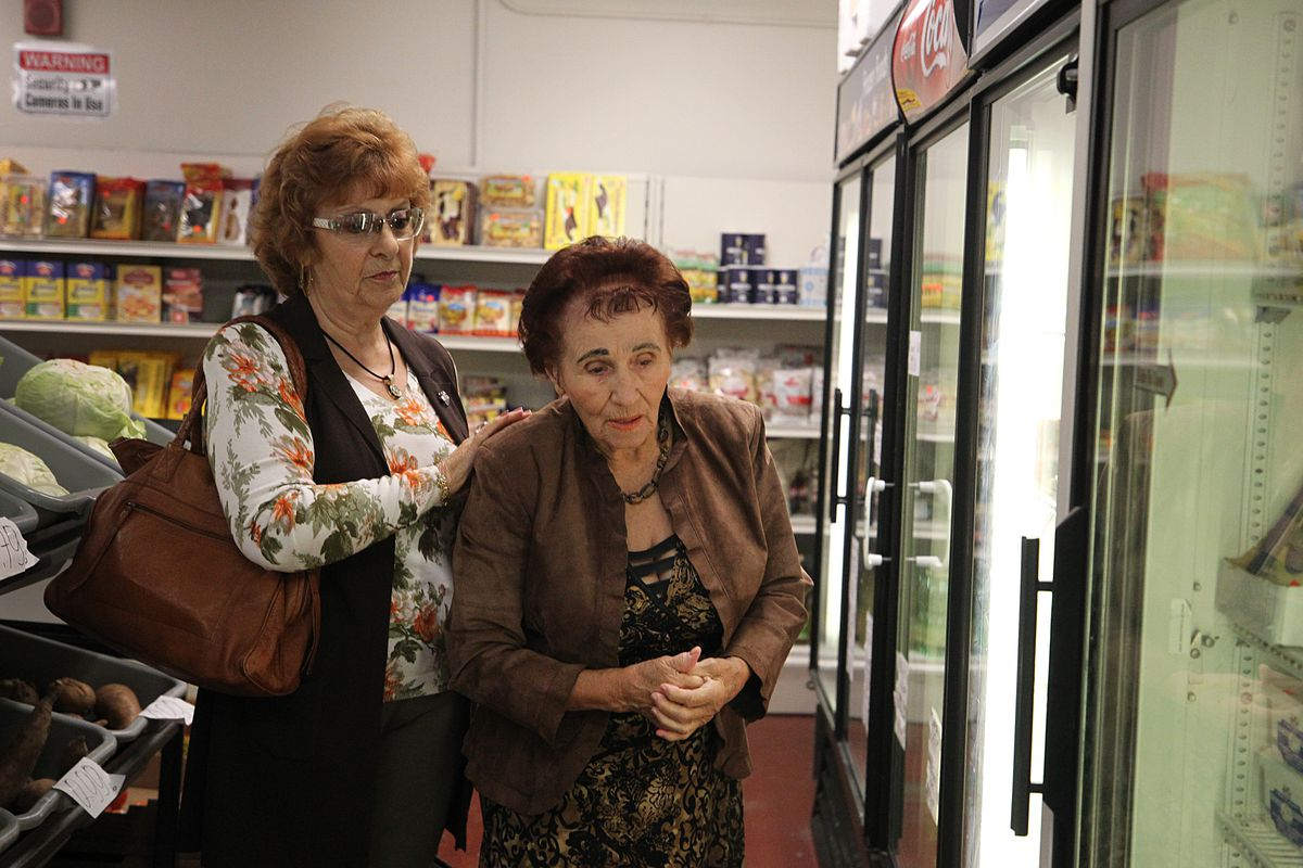 A home health aid places her hands on her elderly client's shoulders to guide her through a grocery store aisle.
