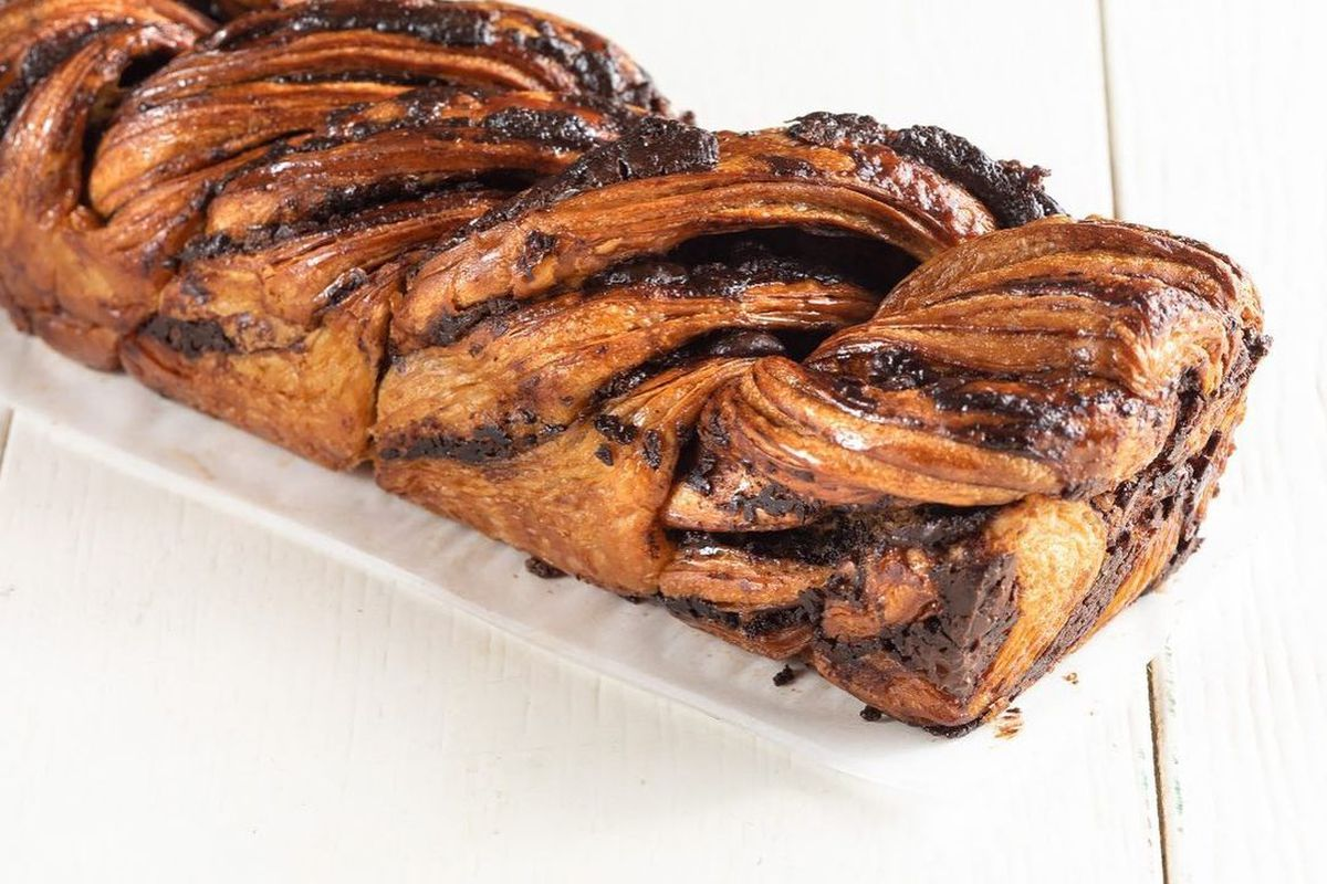 A loaf of babka with chocolate stripes sits on a white tabletop.