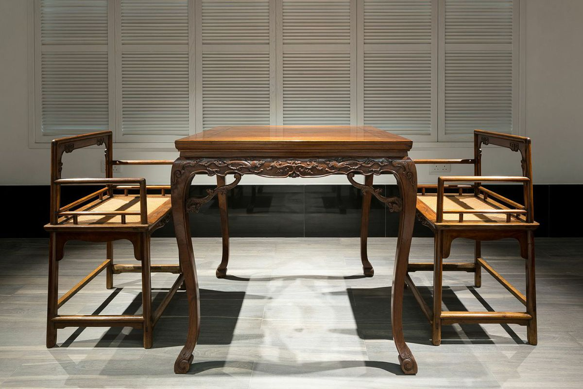 A table with a design carved into the base and two chairs at the Liang Yi Museum.