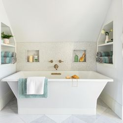 A freestanding soaker nestles under the sloping roof in the main bath, making the most of the room's square footage.