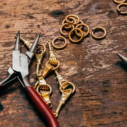 I have a signature grouping that I do using these little hands. I use them for necklaces, earrings, rings, and bracelets. Here I am in the process of joining the two hands together, linking them with a ring to create a very long gold chain. I use the plie