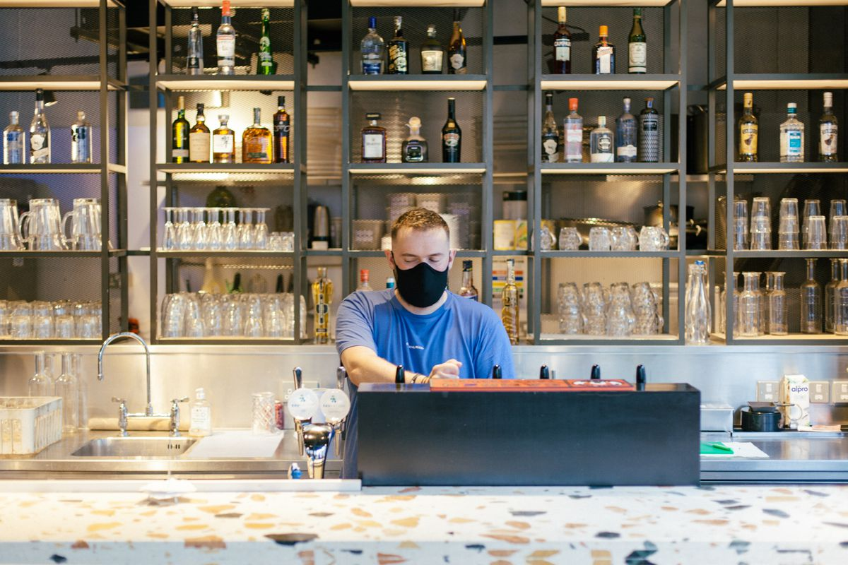 Masked staff behind a terrazzo countertop putting in an order on a till at Homeslice