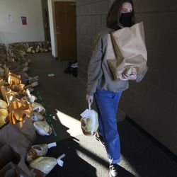 Megan Palmer carries food at a Crossroads Urban Center food distribution event at Rowland Hall in Salt Lake City on Wednesday, Dec. 23, 2020. This year's Christmas food distribution marks the 23rd year of collaboration with Rowland Hall. Crossroads has been providing social services to individuals and families in need in Salt Lake City and the surrounding areas for over 50 years. Funding and support for the Christmas food distribution came from the staff, students and families of Rowland Hall, the Utah Food Bank, the Eccles Broadcast Center at the University of Utah, the B.W. Bastian Foundation, Rocky Mountain Power, and dozens of other individuals and local religious congregations.
