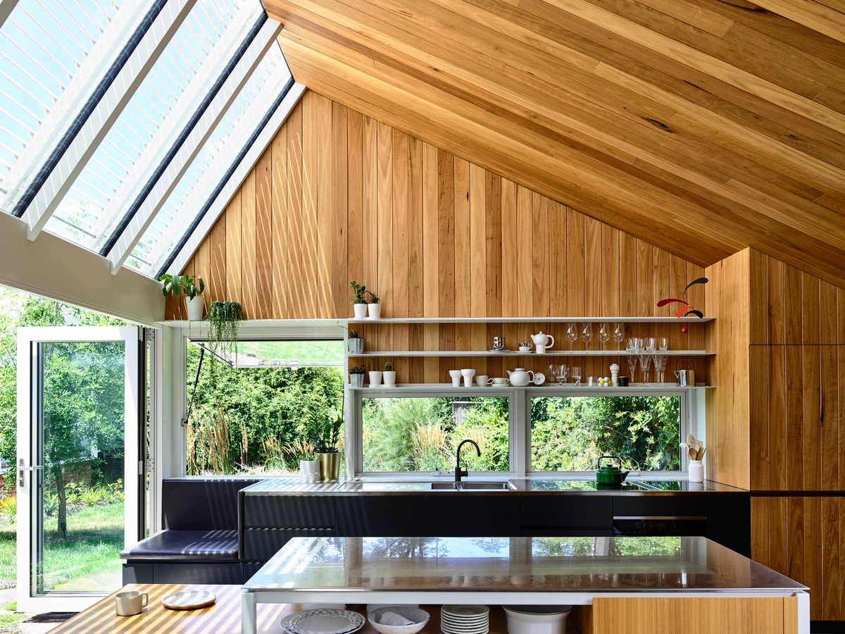 A kitchen with slanted wood ceiling and skylights contains black cabinetry and open shelving.
