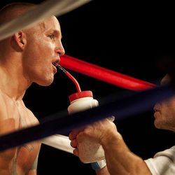 """Allen Litzau gets water from his trainer during his boxing match against Chris """"KidKayo"""" Fernandez at the South Towne Expo Center. Fernandez won the bout after four rounds, Saturday, Dec. 15, 2012."""