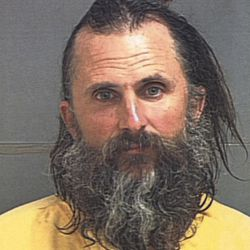 Brian David Mitchell poses for his police booking mug Wednesday, March 12, 2003, in Salt Lake City.