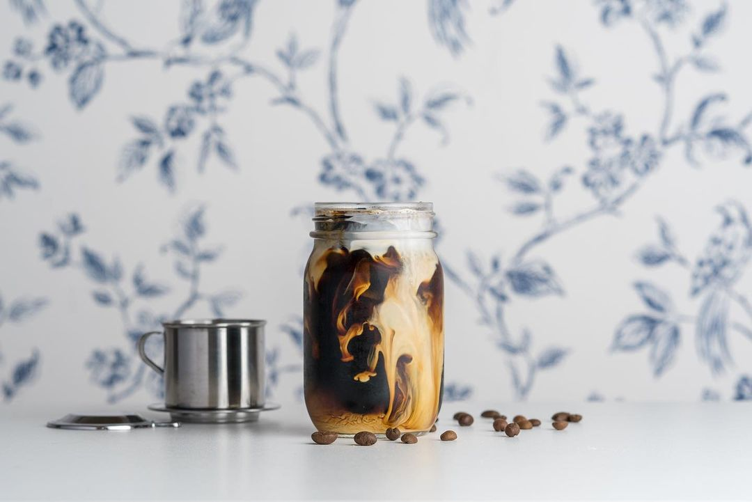 A glass jar full of coffee with a dramatic swirl of cream is on a white surface. A white wall with a blue floral pattern is visible in the background. Coffee beans are scattered across the surface.