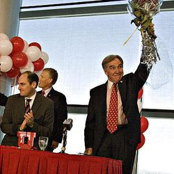 University of Utah President Michael Young holds up a bouquet of roses presented to him by the organizer for the Rose Bowl at a press conference announcing the university's acceptance of the invitation to join the Pac-10 Athletic Conference at the Rice Eccles Stadium on the campus of the University of Utah in Salt Lake City.