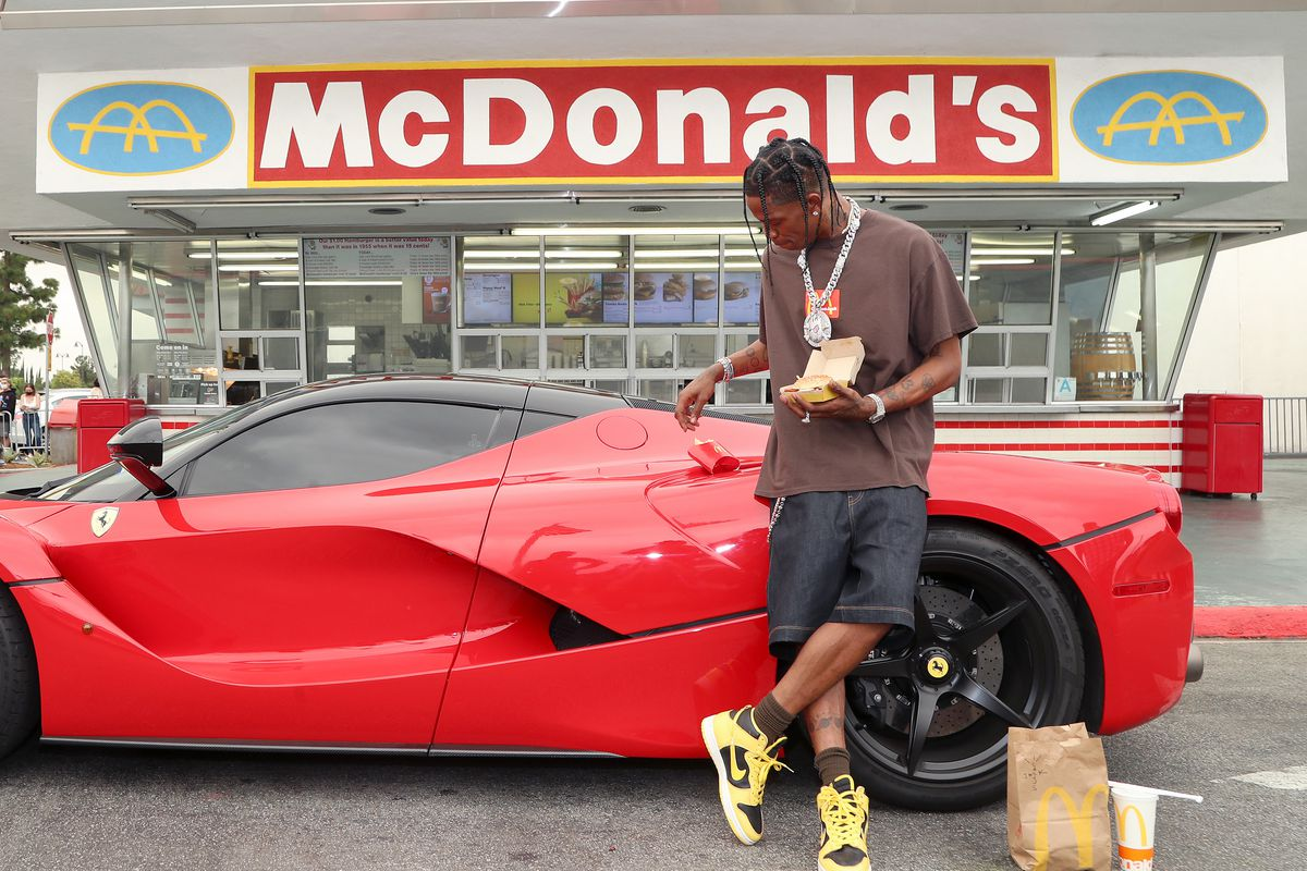 Travis Scott, wearing a brown t-shirt and black shorts, stands in front of a red sports car, which is parked in front of mcdonald's.