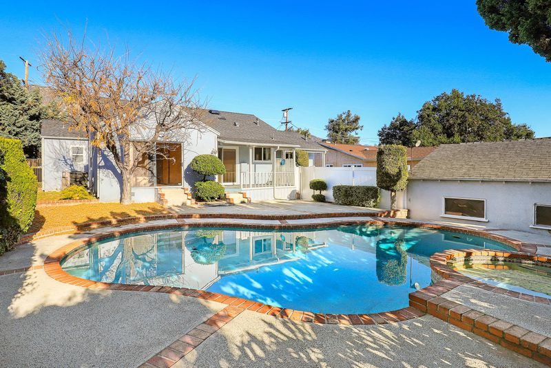 A backyard with a pool dominating the space. In the background is the house and the detached garage.