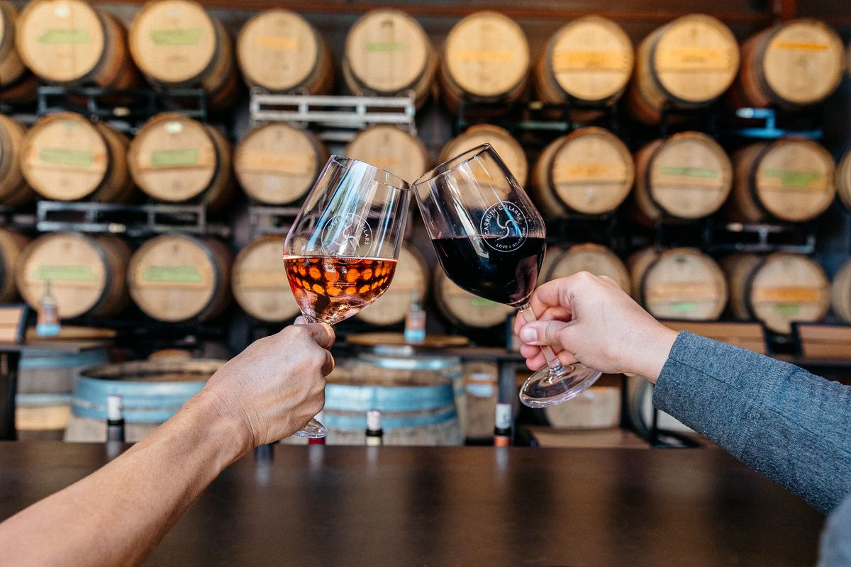 Two people clink wine glasses in front of wine barrels.