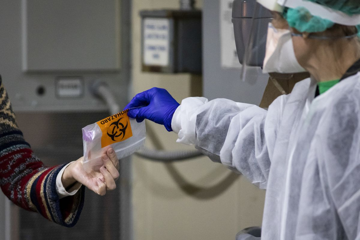 Rush University Medical Center staff collect nasopharyngeal swab samples to test people for the coronavirus at the hospital's drive-thru testing site in November. Experts have found a more infectious strain of the virus in Illinois.