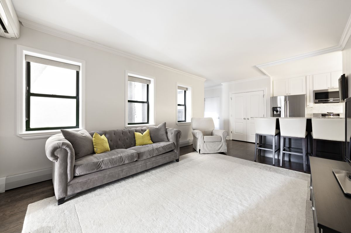 A living area with a beige rug, a grey couch, three windows, and hardwood floors.