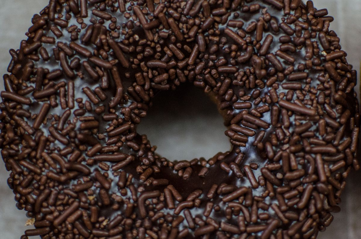 Closeup overhead of a chocolate frosted doughnut with chocolate sprinkles