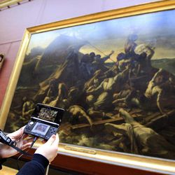 """A visitor studies a painting """"The Raft of the Medusa"""" by French artist Theodore Gericault 1791 - 1824 with the help of the new audio guide at the Louvre Museum in ParisThursday April 12, 2012. The famed Paris museum is going 3D visual with its electronic guides in a deal with Japan's Nintendo to provide game consoles to help visitors who navigate its labyrinthine halls by the millions each year. The guides, in seven languages, and accompanying headsets cost Euro5 ($6.50) on top of the museum's Euro10 standard admission price."""