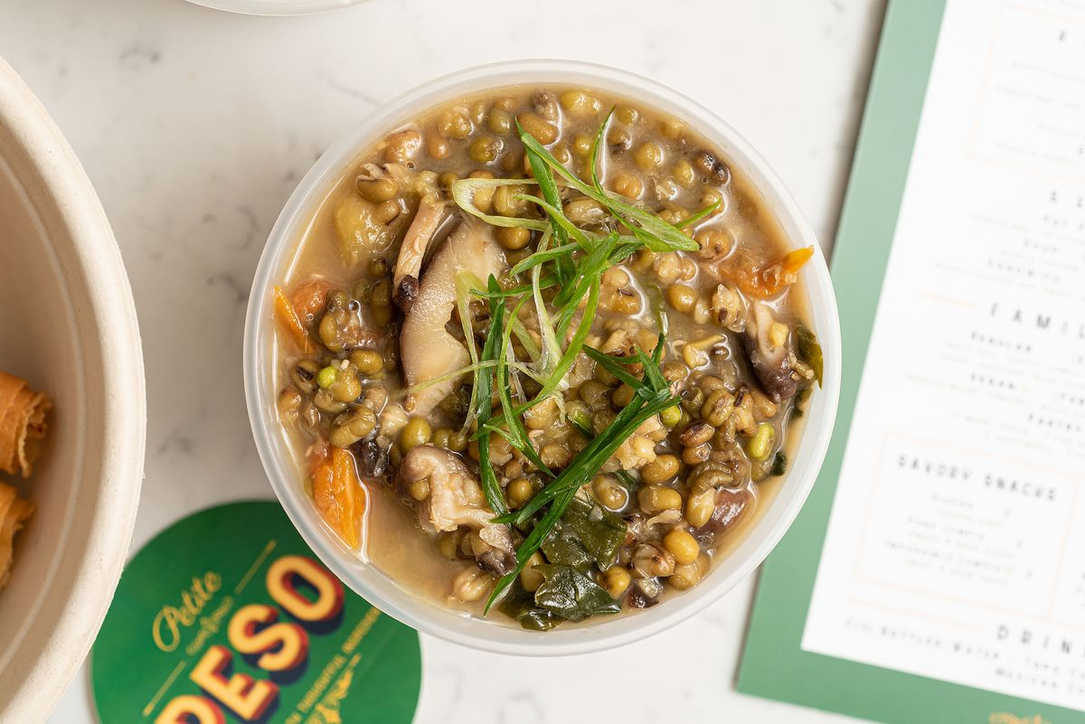 A barley and mushroom bowl sits in the middle of a crowded food table.