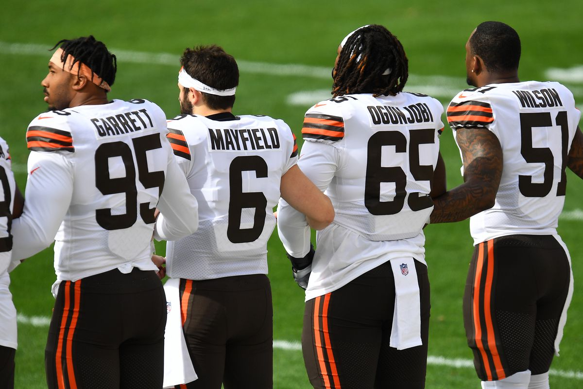 Myles Garrett #95, Baker Mayfield #6, Larry Ogunjobi #65, and Mack Wilson #51 of the Cleveland Browns link arms on the sidelines prior to their NFL game against the Pittsburgh Steelers at Heinz Field on October 18, 2020 in Pittsburgh, Pennsylvania.