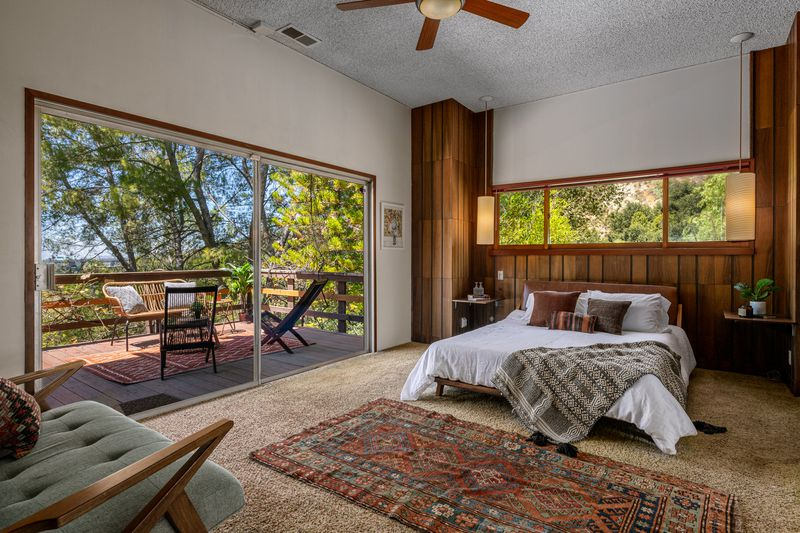 Bedroom with wood-paneled walls and large deck.