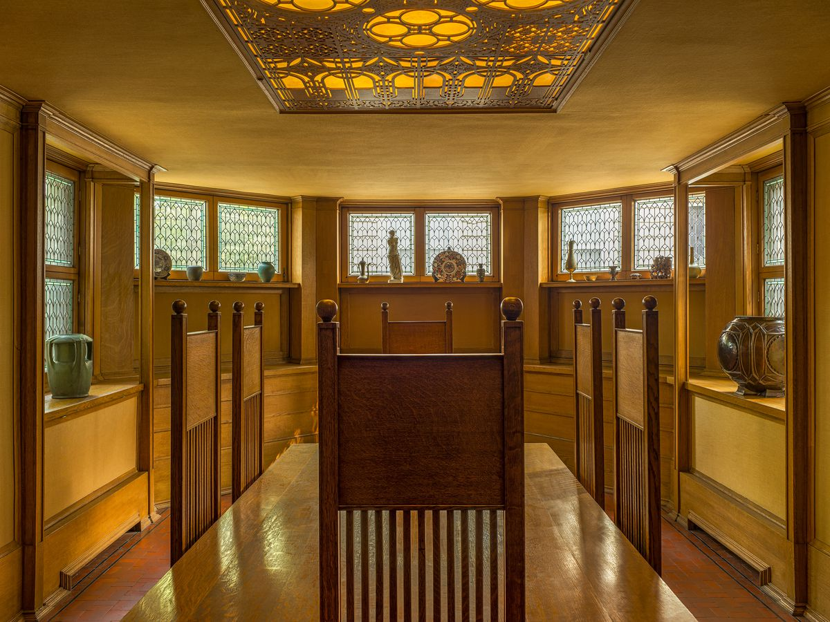 Frank Lloyd Wright Home and Studio. The room has a large table with chairs. There are windows with ornamentation on the walls. On the ceiling is an ornamental light fixture.