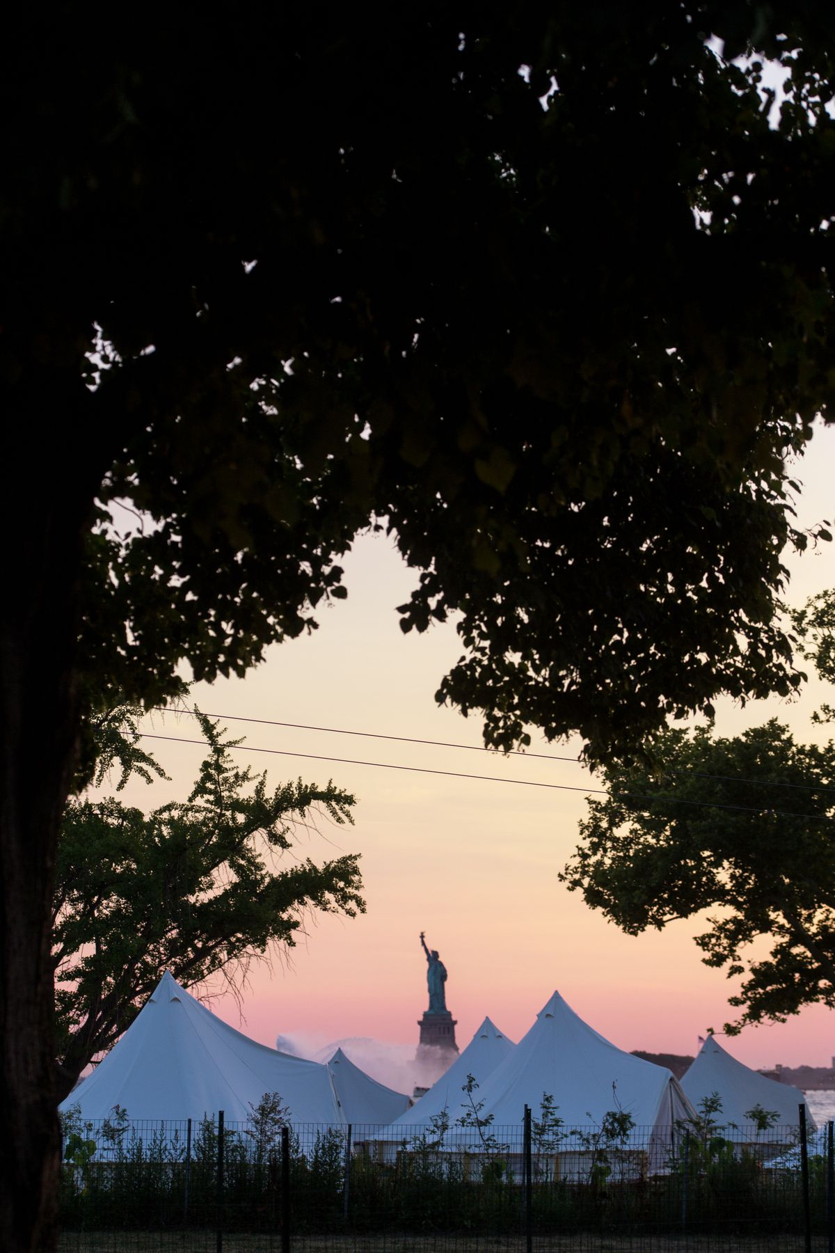Sunset view of glamping tents with Statue of Liberty in the background.