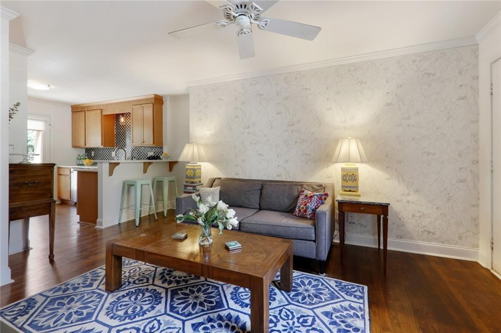 Living area with couch, coffee table, and blue and white area rug.