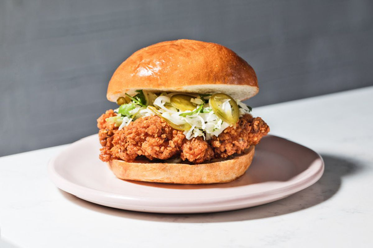 Daybird fried chicken sandwich with coleslaw on a pink plate.