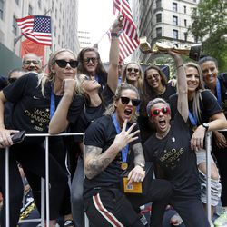 Megan Rapinoe holds the Women's World Cup trophy as the U.S. women's soccer team is celebrated with a parade along the Canyon of Heroes, July 10, 2019, in New York.