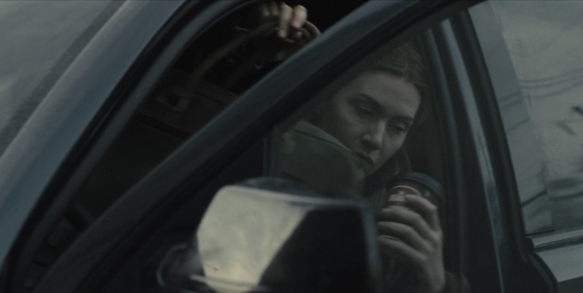 mare of easttown played by kate winslet getting out of a car drinking a wawa coffee