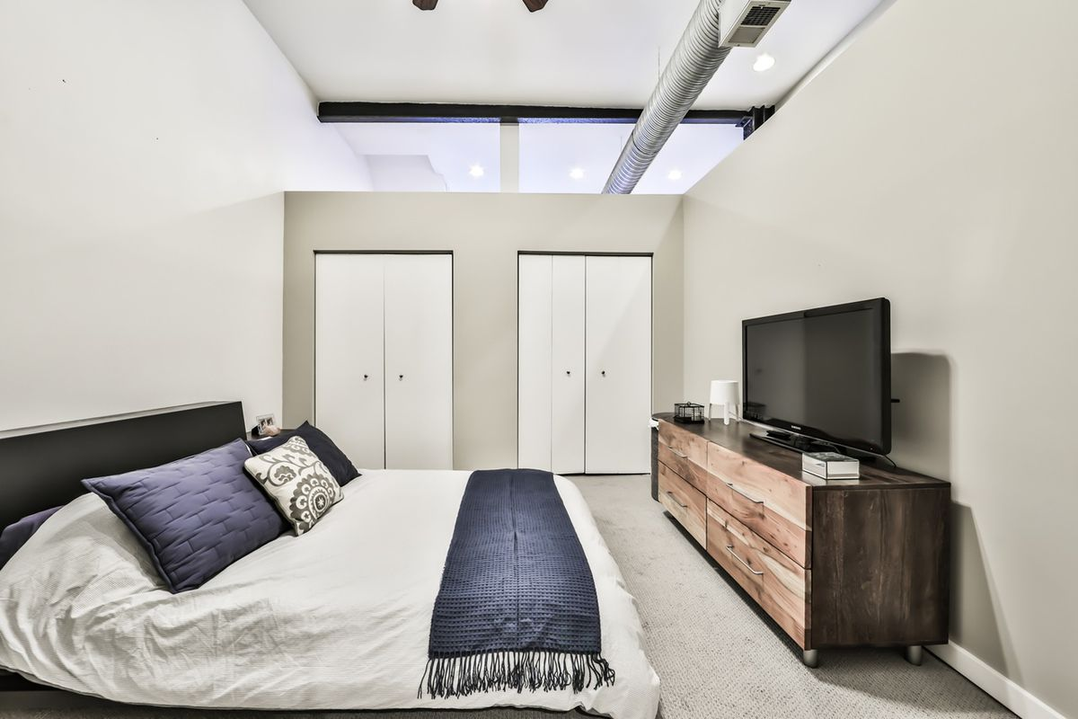 A lofted bedroom with a bed, a wooden dresser, and two closets.