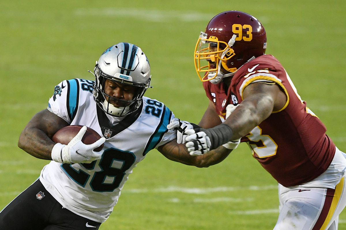 Mike Davis #28 of the Carolina Panthers stiff arms Jonathan Allen #93 of the Washington Football Team at FedExField on December 27, 2020 in Landover, Maryland.
