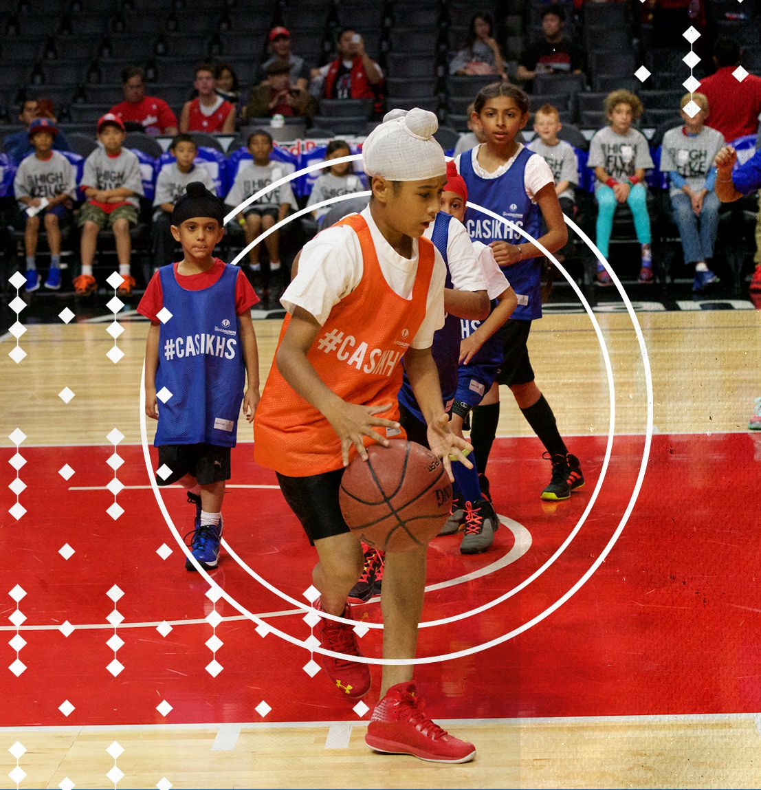 A Sikh boy, his head wrapped in a turban, dribbling a basketball during a scrimmage on the Clippers' home floor.