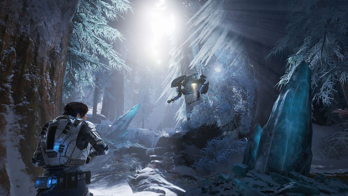 Kait walks through an ice forest in Gears 5 with a robot hovering above her