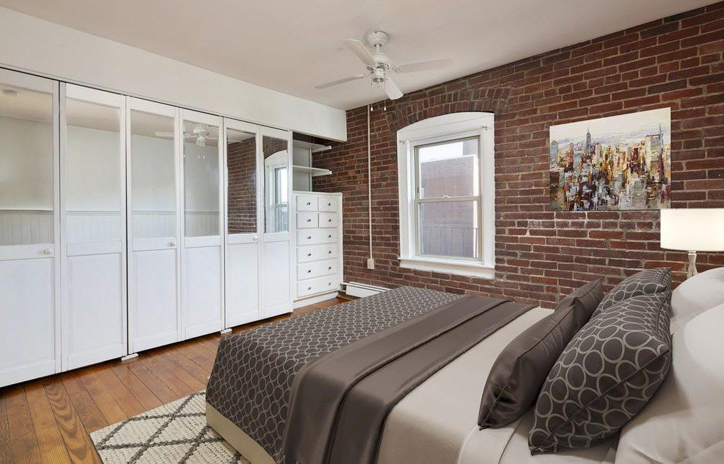 A bedroom with a bed facing a row of glass and wood closet doors.