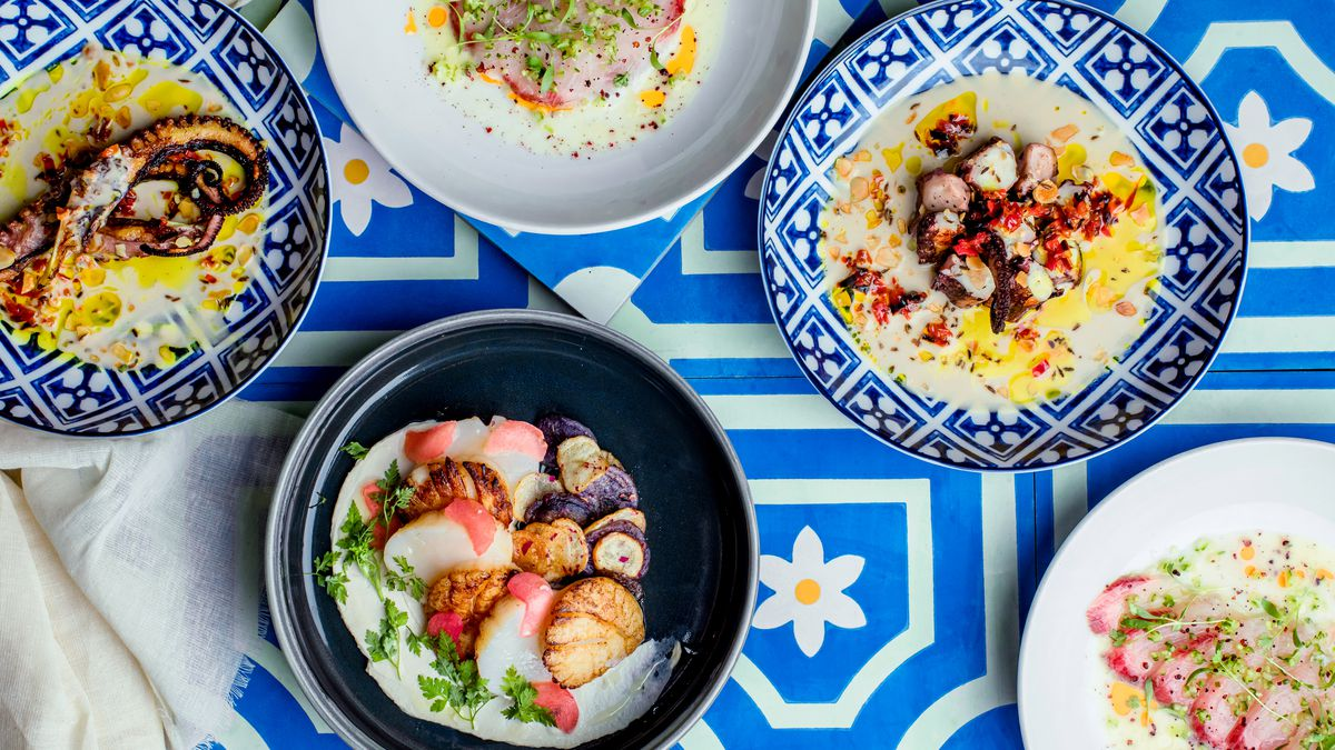 Colorful patterned plates hold seafood dishes from Ilili