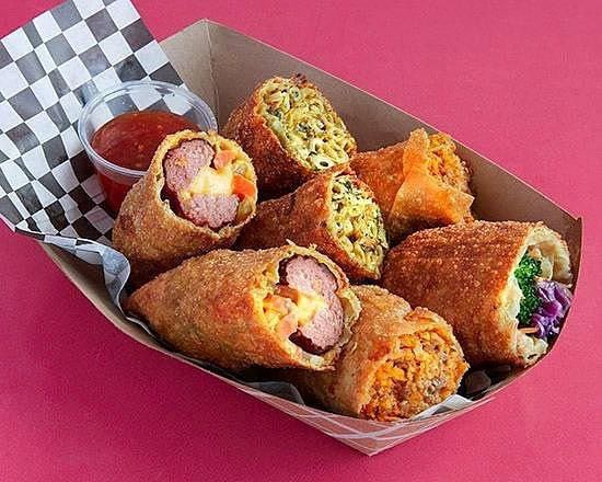 A small paper boat filled with soulrolls, crispy egg roll wrappers stuffed with mac and cheese with greens, hot link and cheese, and vegetables